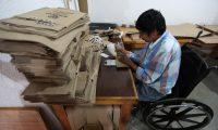 Diego Ramírez Xicay trabaja en el pegado de las bolsas en la Asociación Adisa, Santiago Atitlán, Sololá. (Foto Prensa Libre: César Pérez)