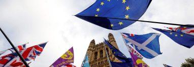 Las banderas de la UE de los activistas anti-Brexit se muestran junto a las banderas de la Unión de activistas pro-Brexit mientras se manifiestan fuera de las Casas del Parlamento en Londres. (Foto Prensa Libre: AFP)