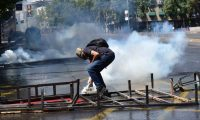 Demonstrators clash with riot police during protests in Santiago, on October 20, 2019. - Fresh clashes broke out in Chile's capital Santiago on Sunday after two people died when a supermarket was torched overnight as violent protests sparked by anger over economic conditions and social inequality raged into a third day. (Photo by Martin BERNETTI / AFP)