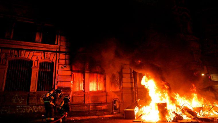 Manifestantes prendieron fuego al diario El Mercurio, el  más antiguo de Chile. (Foto Prensa Libre: AFP)