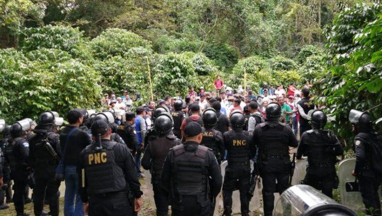 Agentes de la PNC dialogan con personas en una ocupación de tierras en Malacatán, San Marcos en 2019. (Foto Prensa Libre: HemerotecaPL).