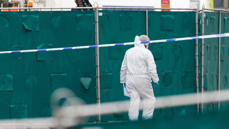 La Policía y agentes forenses investigan la escena en el Parque Industrial Waterglade en Grays, Essex, Gran Bretaña, donde se descubrieron 39 cuerpos dentro de un contenedor de camión. (Foto Prensa Libre: AFP)