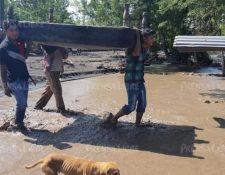 Pobladores de la aldea El Socorro tratan de rescatar algunas de sus pertenencias dañadas por el material volcánico. (Foto Prensa Libre: Enrique Paredes).