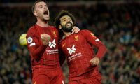Liverpool's Egyptian midfielder Mohamed Salah (R) celebrates with Liverpool's English midfielder Jordan Henderson after scoring a penalty during the English Premier League football match between Liverpool and Tottenham Hotspur at Anfield in Liverpool, north west England on October 27, 2019. (Photo by STRINGER / AFP) / RESTRICTED TO EDITORIAL USE. No use with unauthorized audio, video, data, fixture lists, club/league logos or 'live' services. Online in-match use limited to 120 images. An additional 40 images may be used in extra time. No video emulation. Social media in-match use limited to 120 images. An additional 40 images may be used in extra time. No use in betting publications, games or single club/league/player publications. /