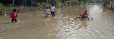 Vecinos de Las Cruces, Petén, camina entre el agua y luego que anega las calles del pueblo, debido a la fuerte lluvia que azota esa región. (Foto Prensa Libre: Conred)