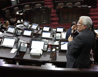 El ministro de la Defensa, Luis Miguel Ralda, sentado del la lado izquierdo pone atención a lo que dice el diputado Oliverio García Rodas, se puede observar la falta de diputados en el hemiciclo. (Foto Prensa Libre: Noé Medina)