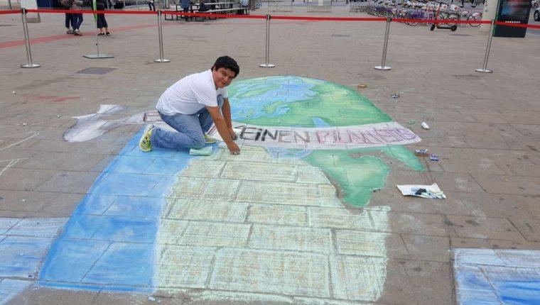 El pintor guatemalteco Gustavo Juárez García muestra una de las pinturas que elaboró en una de las principales plazas de Viena. (Foto Prensa Libre: Cortesía).