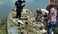 Personal de la Autoridad para el Manejo  y Desarrollo Sostenible de la Cuenca del Lago Petén Itzá recoge desechos que fueron arrastrados por las correntadas.   (Foto Prensa Libre:  Dony Stewart)