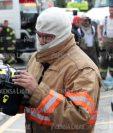 Uno de los bomberos revisa su equipo de protección luego del incendio. (Foto Prensa Libre: Esbin García)