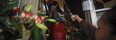 La imagen de madera de San Simón es cubierta con un plástico transparente durante su celebración. (Foto Prensa Libre: AFP)