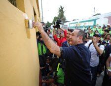 El presidente electo Alejandro Giammattei pinta una de las casas por donde pasará el tren junto al alcalde capitalino Ricardo Quiñónez. (Foto Prensa Libre: Municipalidad de Guatemala)