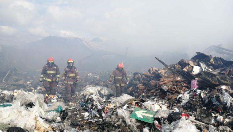 Bomberos caminan revisando los escombros para detectar focos de fuego. (Foto Prensa Libre: Andrea Domínguez)