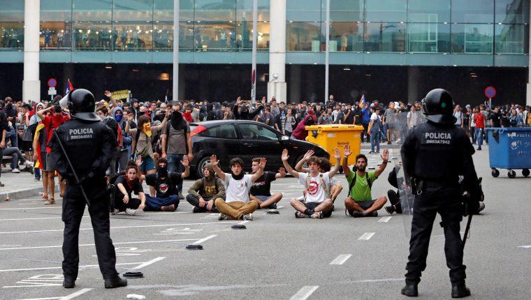 Autoridades controlan a las personas que se concentraron en el Aeropuerto del Prat, Barcelona. (Foto Prensa Libre: EFE)