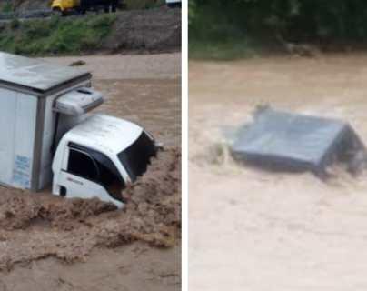 Río crecido arrastra un camión y una camioneta agrícola