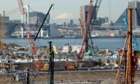 A snow-capped Mount Fuji (C) is pictured behind a construction site in Tokyo on February 16, 2015. Japan's economy limped out of recession in the last quarter of 2014, official data showed on February 16, but annual growth was flat and the weaker-than-expected figures were likely to boost calls for more central bank stimulus.     AFP PHOTO / Yoshikazu TSUNO