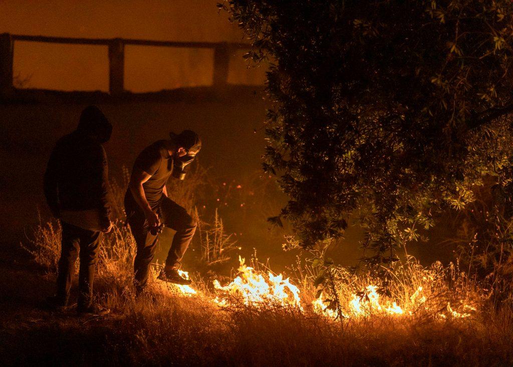 Un hombre pisa las llamas del incendio de Saddleridge en la sección Porter Ranch de Los Ángeles, California, en las primeras horas de la mañana del 11 de octubre de 2019. (Foto Prensa Libre: AFP)