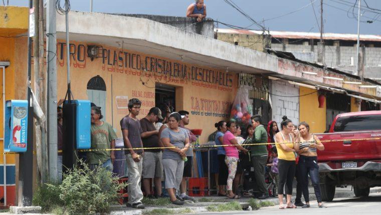 Vecinos de Villa Hermosa observan el trabajo del Ministerio Público en el lugar donde murió un trabajador la mañana del martes 8 de octubre. (Foto Prensa Libre: Óscar Rivas)