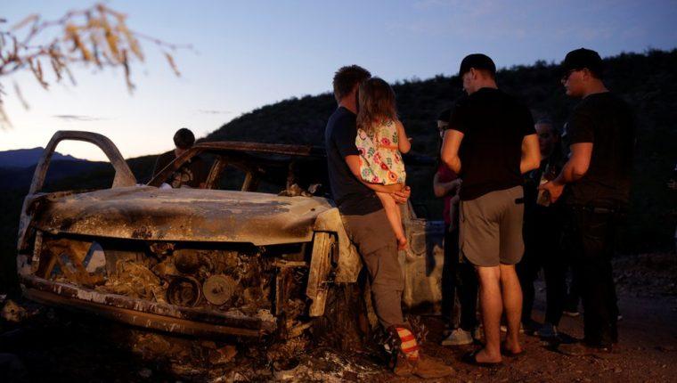 Los familiares de las víctimas frente a uno de los vehículos que resultó incendiado en la emboscada.