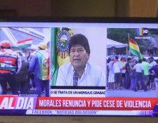 Ciudadanos bolivianos observan en una pantalla la renuncia del presidente de Bolivia, Evo Morales. EFE/Martin Alipaz