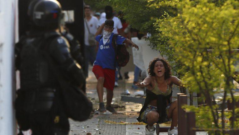 Una mujer grita entre un manifestante que enfrenta a la policía durante el desarrollo de las protestas y movilizaciones por el denominado Paro Nacional. (Foto Prensa Libre: EFE)