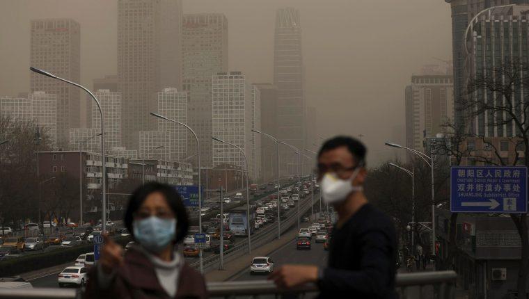 Un hombre y una mujer se protegen con máscaras de la nube de contaminación que cubre la ciudad de Pekín. (Foto Prensa Libre: EFE)