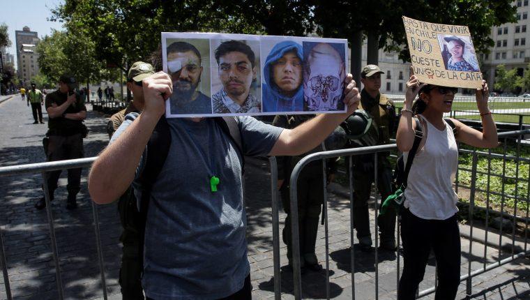 Manifestantes portan carteles con fotografías de algunos de los más de 200 heridos oculares, con pérdida parcial o total de la visión por el uso de balines y otras municiones utilizadas por Fuerzas Especiales de Carabineros. (Foto Prensa Libre: EFE)