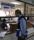 Dos trabajadores de Gestión Penal atienden la solicitud de un visitante en Torre de Tribunales, los empleados de esa sección también serian beneficiados con el bono navideño.  (Foto Prensa Libre: Alejandra Arriola)