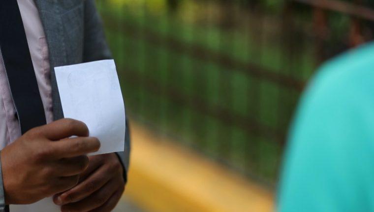 Unas de las víctimas de las estafa muestras el baucher del depósito bancario a la supuesta reclutadora por Q140. (Foto Prensa Libre: Miriam Figueroa)