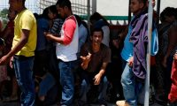 """Honduran migrants wait at the international border bridge in Ciudad Tecun Uman, Guatemala, as they wait to cross into Mexico on April 12, 2019. - A group of 350 Central American migrants forced their way into Mexico Friday, authorities said, as a new caravan of around 2,500 people arrived -- news sure to draw the attention of US President Donald Trump. Mexico's National Migration Institute said some members of the caravan had a """"hostile attitude"""" and had attacked local police in the southern town of Metapa de Dominguez after crossing the border from Guatemala. (Photo by Rodrigo Mendez / AFP)"""