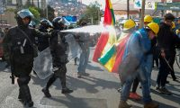 Riot police fire tear gas to disperse people taking part in a blockade to protest against the results of the October 20 elections in La Paz, on November 4, 2019. - Bolivia's government accused its rivals Sunday of plotting deadly violence against it after an opposition figure vowed to oust leftist President Evo Morales and called for the military's support. Deadly unrest has gripped the South American country since Morales was named winner of the October 20 election for a fourth term. (Photo by JORGE BERNAL / AFP)