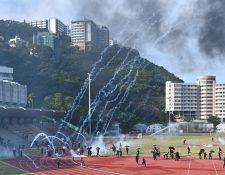 Protestantes corren mientras las bombas de gas caen en la Universidad  de Hong Kong (CUHK). (Foto Prensa Libre: AFP)