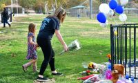 "Flowers are dropped off at a makeshift memorial in Central Park, not far from Saugus High School on November 15, 2019 in Santa Clarita, California - A teenage boy gunned down fellow students at a California high school on his 16th birthday on November 14, 2019, killing two and wounding another three before turning the pistol on himself. The gunman was taken into custody in ""grave"" condition, police said, as officers stormed Saugus High School in Santa Clarita -- the latest in a relentless cycle of classroom shootings that have left around 300 youngsters dead over two decades. (Photo by Frederic J. BROWN / AFP)"