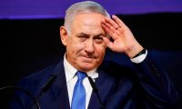 """(FILES) In this file photo taken on April 10, 2019 Israeli Prime Minister Benjamin Netanyahu gestures as he addresses supporters at his Likud Party headquarters in the Israeli coastal city of Tel Aviv. - Netanyahu, Israel's longest-serving prime minister, is a right-wing politician and former elite soldier nicknamed """"Mr Security"""" and a close ally of US President Donald Trump. As of November 21, the 70-year-old is also the first premier in Israeli history to be indicted in office, accused of corruption charges that could end the veteran leader's political career. The burly son of a historian with the familiar grey comb-over and deep voice has entrenched himself at the top so firmly he has been labelled """"King Bibi"""", referring to his childhood nickname of Bibi. (Photo by Thomas COEX / AFP)"""