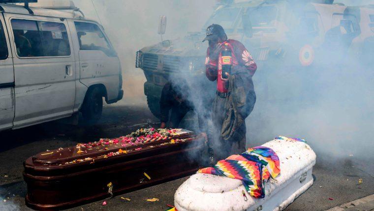 Los familiares de las víctimas muertas corrieron para resguardarse y los ataúdes quedaron en el suelo. (Foto Prensa Libre: AFP)