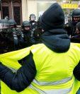 Uno de los manifestantes de los chalecos amarillos frente a la Policía em París. (Foto Prensa Libre: EFE).