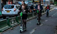 People ride electric scooters in Bogota on June 26, 2019. - The use of the increasingly-popular electric scooters, which offer a quick and cheap way to get around, is causing safety concerns in cities across Latin America. Critics say they pose a grave safety risk both for users and pedestrians while authorities in some countries have started implementing some kind of framework for their use. (Photo by Juan BARRETO / AFP)