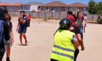Una madre, con chaleco amarillo, saca a su hija de una protesta. Redes