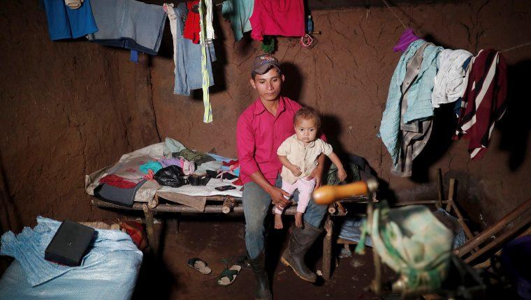 La niña Carla, de 4 años, es cargada por su padre adoptivo, Roque, en la única habitación de su casa de adobe y tierra, en el caserío El Ceibal, Jocotán, Chiquimula. (Foto Prensa Libre: EFE)