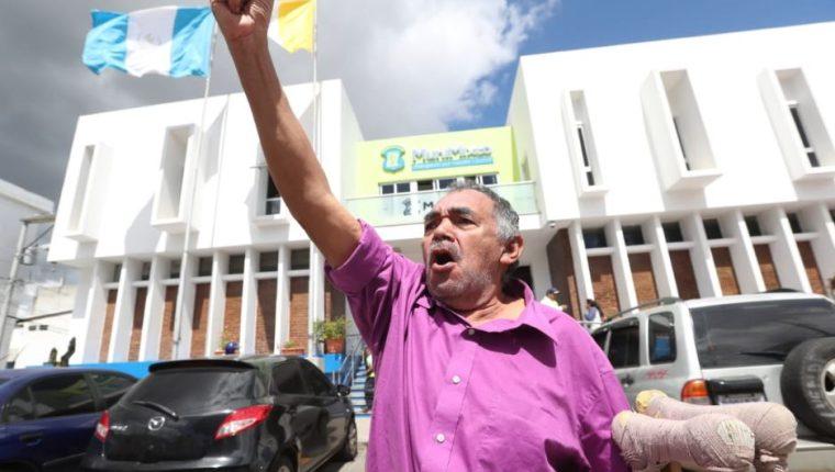 El exempleado Carlos Arturo Hernández, quien usa muletas por un accidente laboral, se manifiesta frente a la comuna de Mixco. (Foto Prensa Libre: Érick Ávila).