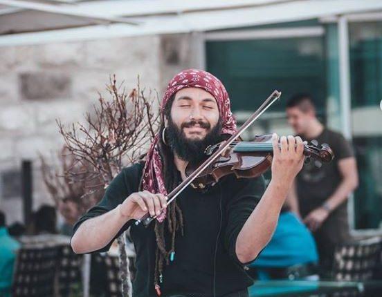 El músico guatemalteco Abdul Medina ejecuta su violín en Budva, Montenegro. (Foto Prensa Libre: Tomada de Instagram).