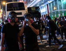 Los manifestantes usan equipo de protección mientras se reúnen en la carretera principal en el distrito Mong Kok de Hong Kong. (Foto Prensa Libre: AFP).