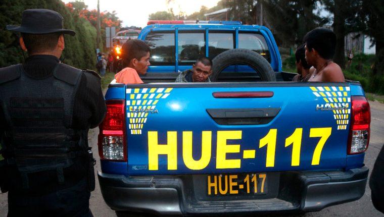 Cuatro hombres esperan su traslado en la parte trasera de una autopatrulla de la Policía Nacional Civil en el km 254 de la Ruta Interamericana, tras ser señalados de intentar asaltar un bus. (Foto Prensa Libre: Mike Castillo)