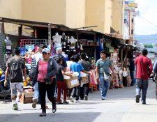 Peatones caminan a la mitad de la calle a un costado de la catedral de Huehuetenango porque las ventas navideñas ocupan las aceras. (Foto Prensa LIbre: Mike Castillo)