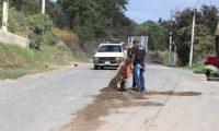 Transportistas rellenan los agujeros en la carretera a San Pedro Jocopilas, Quiché con arena, (Foto Prensa Libre: Héctor Cordero)