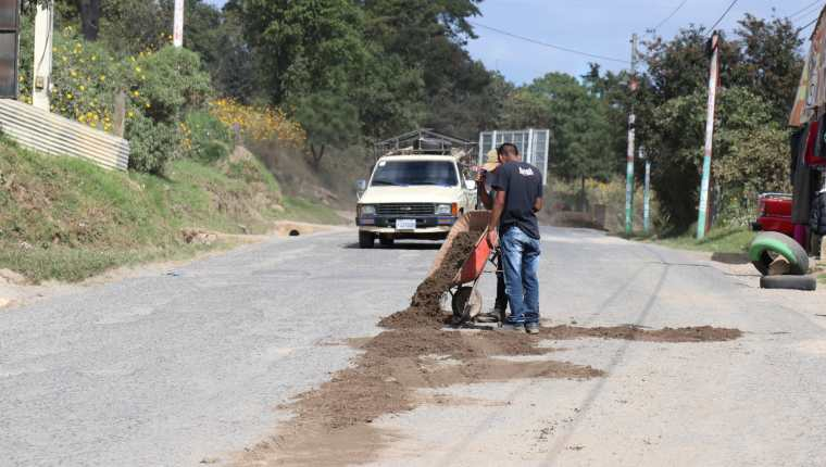 Transportistas rellenan los agujeros en la carretera a San Pedro Jocopilas, Quiché con arena,  (Foto Prensa Libre: Héctor Cordero).