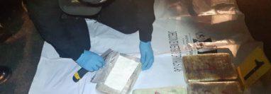 Un agente de la Policía inspecciona uno de los cuatro paquetes con cocaína. (Foto Prensa Libre: PNC)