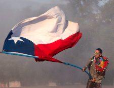 Un ciudadano chileno hondea la bandera nacional en el centro de Santiago de Chile durante las protestas. (Foto Prensa Libre: AFP)