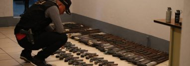 Un agente de la PNC revisa parte de las armas incautadas. (Foto Prensa Libre: PNC)