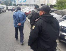 Policías conducen a uno de los detenidos por el caso de estafa a la Torre de Tribunales (Foto Prensa Libre: Cortesía PNC).