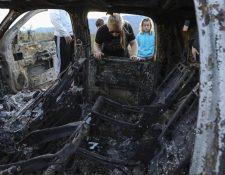 Familiares de los masacrados en México observan el estado en que quedaron los vehículos. (Foto: AFP)